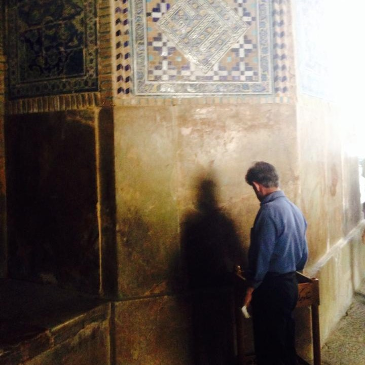 A worshiper in Esfahan chooses a Turbah stone, a clay tablet used in the prayer rituals of Shiite Islam