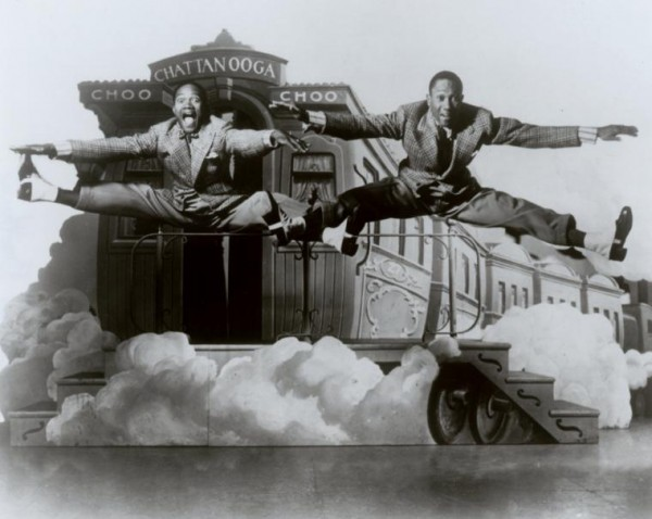"The Nicholas Brothers in side split leaps in front of a stage set featuring a railroad caboose labeled ""Chatanooga Choo Choo,"" 1941."