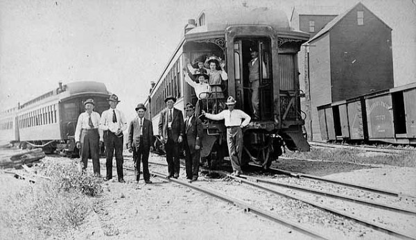 A postcard showing men and women standing on and by a caboose, circa 1908.