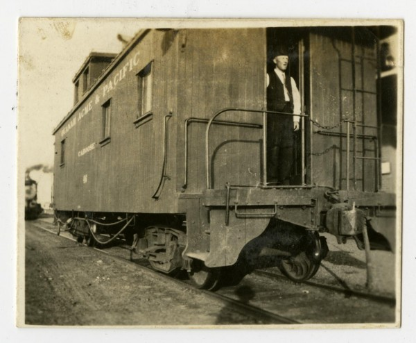 A conductor wearing a dark hat and vest stands in the doorway of a caboose labeled Quanah, Acme and Pacific Railway. A smoking locomotive can be seen in the background,1909.